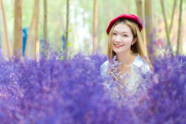 A bela jovem asiática sorri enquanto fica parada no jardim de flores roxas como uma flor de lavanda
