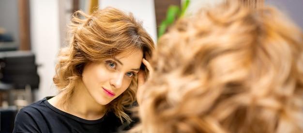 A bela jovem caucasiana olha para seu reflexo no espelho, verificando o penteado e a maquiagem em um salão de beleza.