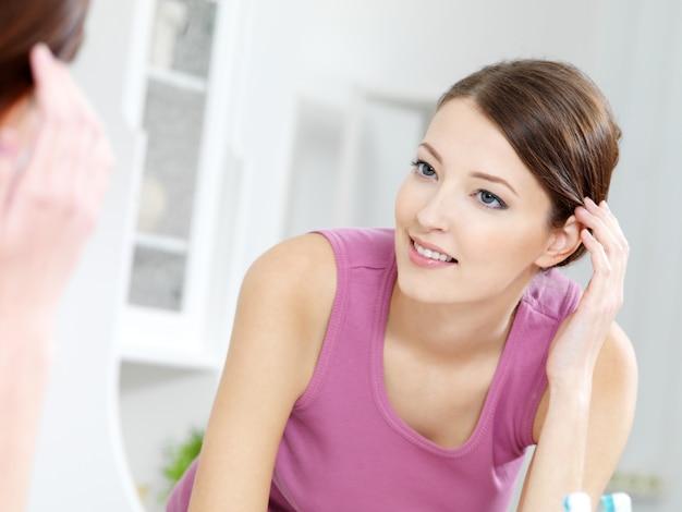 A bela jovem com rosto limpo e fresco em pé em frente a um espelho em um banheiro