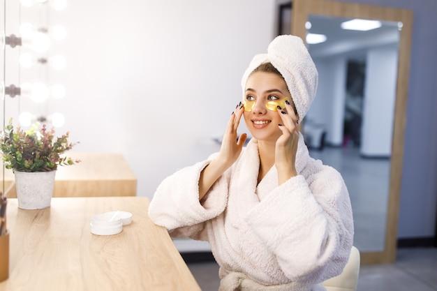 A bela jovem cuida da pele usando adesivos sob os olhos em casa