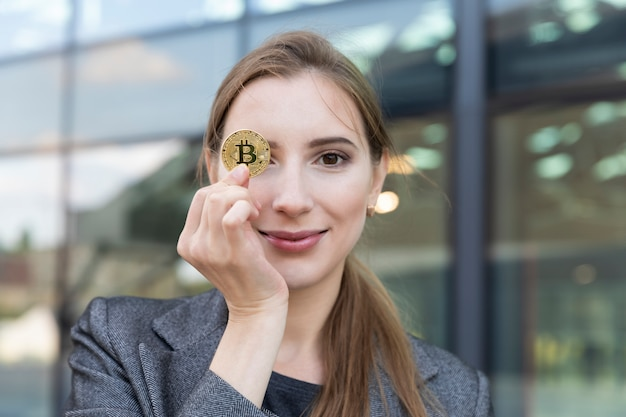A bela jovem detém bitcoin em uma mão. ela é uma mulher de negócios e investiu seu dinheiro em criptomoeda, planejando ganhar um bom dinheiro com isso.