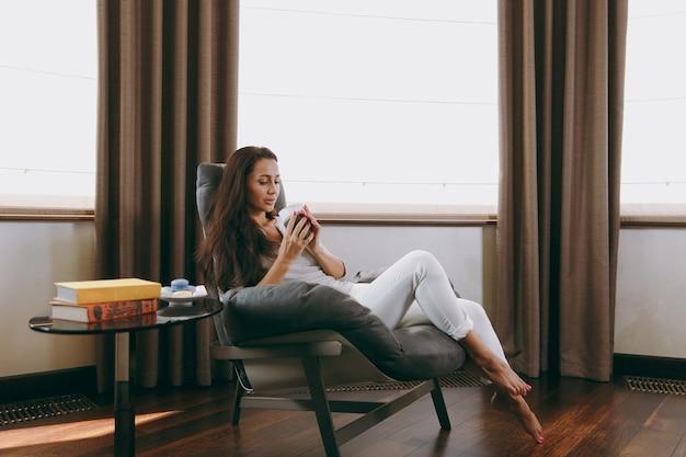 A bela jovem em casa sentada em uma cadeira moderna em frente à janela, relaxando na sala de estar e bebendo café ou chá