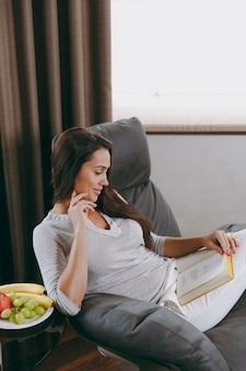 A bela jovem em casa sentada em uma cadeira moderna em frente à janela, relaxando na sala de estar e lendo um livro