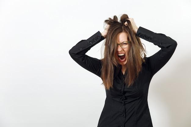A bela jovem europeia de cabelos castanhos com raiva de óculos para visão com pele limpa e saudável, vestida com uma camisa preta escura, gritando e xingando, sobre um fundo branco. conceito de emoções.