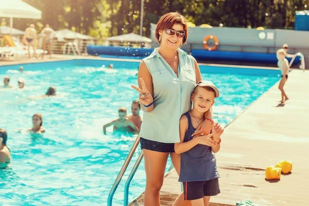 A bela jovem mãe ensinando seu filho a nadar na piscina