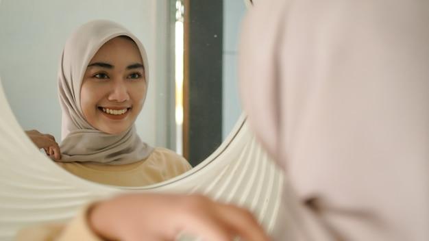 A bela jovem muçulmana sorri docemente no espelho
