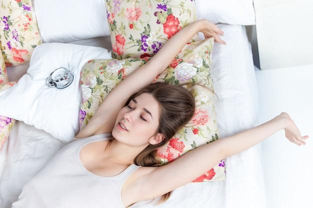 A bela jovem na cama com o serviço do relógio em casa