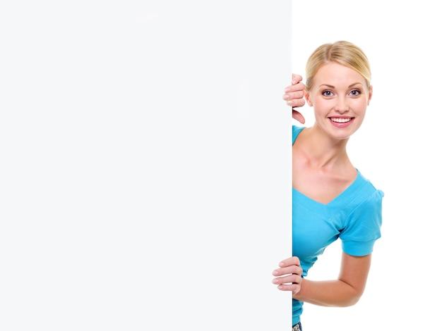 A bela jovem sorridente olha para fora por causa de um banner branco de publicidade vazio