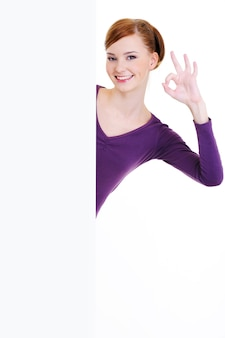 A bela jovem sorridente olha por causa de um banner de publicidade em branco com um gesto de ok