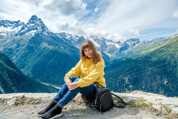 A bela jovem viaja sozinha nas montanhas na primavera ou no outono e senta-se na borda
