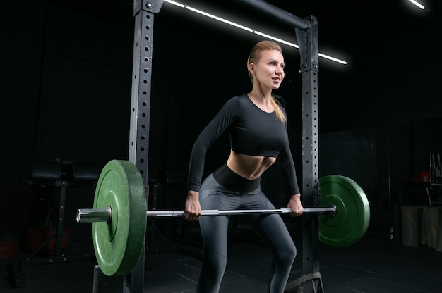 A bela loira alta realiza um exercício chamado levantamento terra. conceito de fitness e musculação. mídia mista