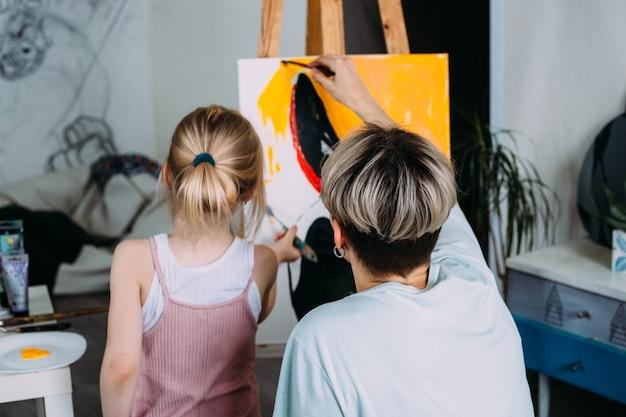 A bela mãe artista e seu filho pintam um quadro em casa com tintas acrílicas