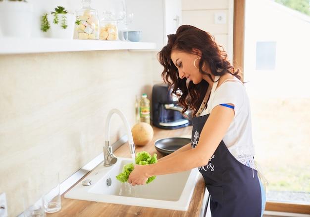 A bela moça lavando uma salada