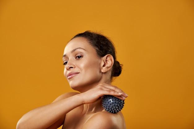 A bela mulher africana fazendo massagem com bola de massagem isolada em backgroung amarelo