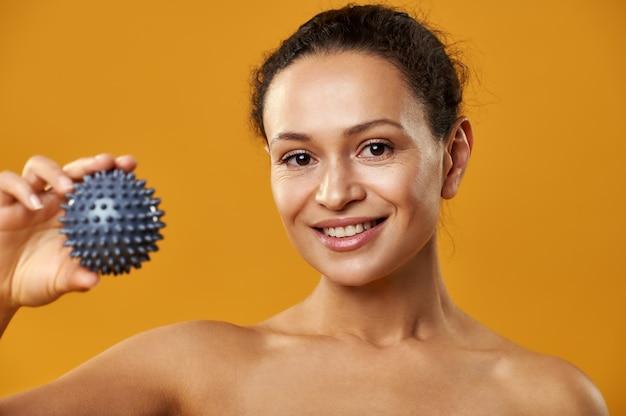 A bela mulher africana mostrando uma bola de massagem para a câmera isolada em um fundo amarelo