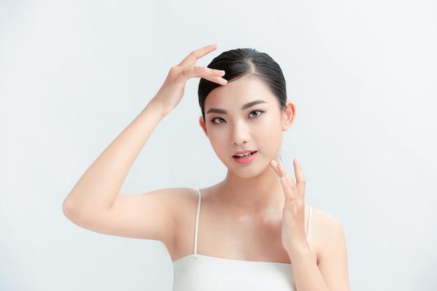 A bela mulher asiática e tem charme de pele branca e parede branca