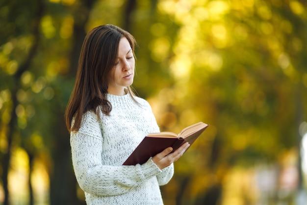 A bela mulher de cabelos castanhos em um suéter branco em pé com um livro vermelho no outono parque da cidade em um dia quente. folhas de outono dourado. conceito de leitura.