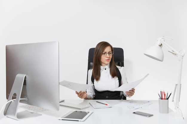 A bela mulher de negócios de cabelos castanhos cansada, perplexa e estressada, de terno e óculos, sentada à mesa, trabalhando em um computador contemporâneo com documentos em um escritório leve
