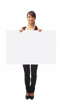 A bela mulher de negócios mostra em uma parede branca