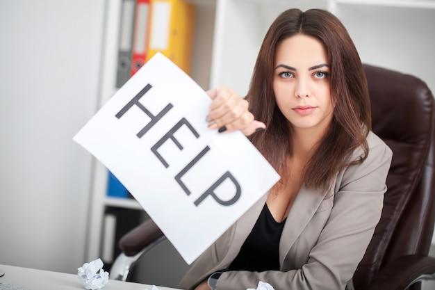 A bela mulher de negócios no escritório pede ajuda
