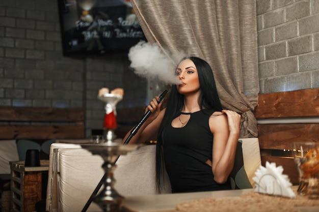 A bela mulher fuma narguilé e deixa a fumaça