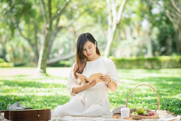 A bela mulher grávida fazendo piquenique e lendo um caderno no jardim