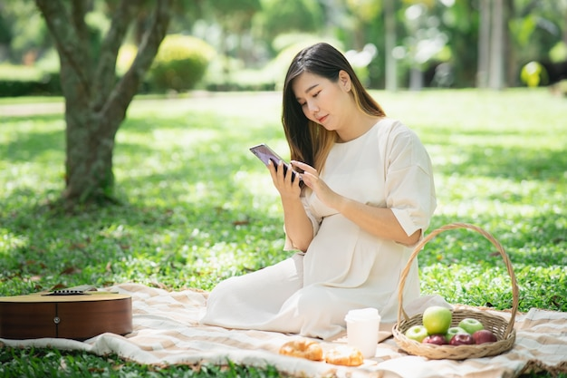 A bela mulher grávida no piquenique e usando o telefone celular no jardim