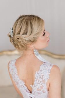A bela mulher posando em um vestido de noiva em um interior luxuoso
