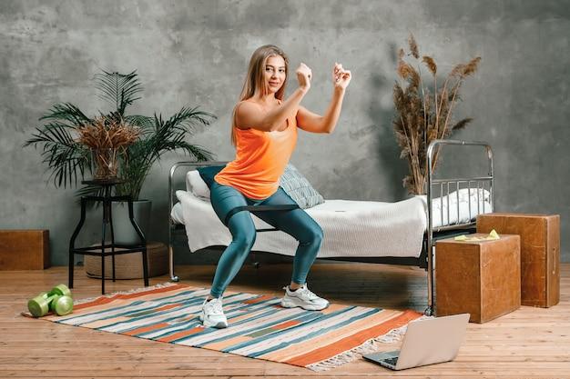 A bela mulher pratica esportes em casa