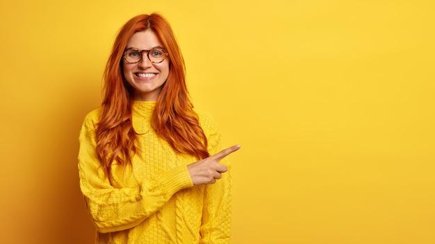 A bela mulher ruiva positiva sorri amplamente aponta para o espaço em branco e recomenda uma boa oferta de venda vestida com uma camisola de malha.