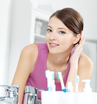 A bela mulher sorridente com o rosto de pele limpa se olhando no espelho em um banheiro