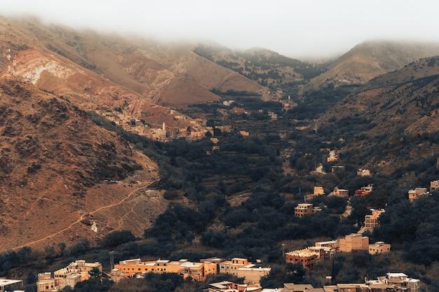 A bela paisagem com montanhas atlas em marrocos com uma pequena aldeia abaixo