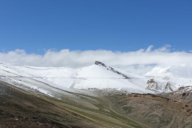 A bela paisagem e o caminho para tanglang la pass, com pico de neve, é a segunda maior estrada motorizada do mundo