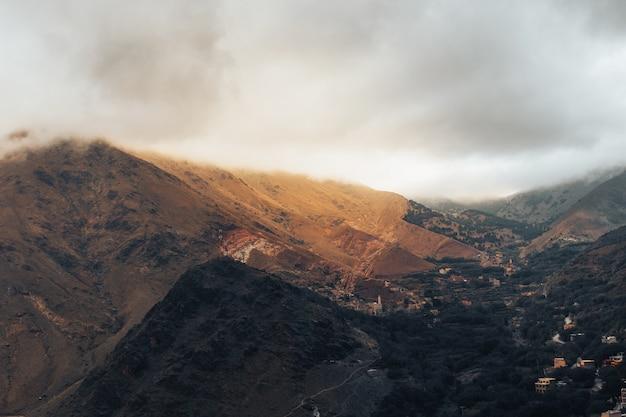 A bela paisagem nublada com as montanhas do atlas marroquino e uma pequena vila abaixo
