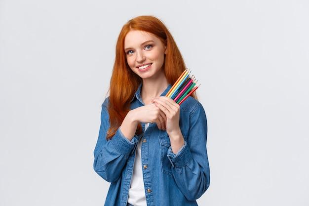 A bela ruiva sonhadora carismática de camisa jeans, olhando pensativa para a câmera e imaginando imagens, quer desenhar algo, tem um projeto de design em mente, segurando lápis de cor,