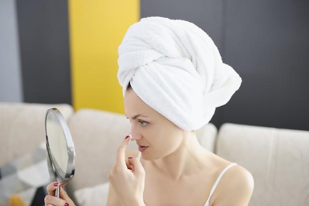 A bela senhora sorridente aplica creme para a pele no rosto enquanto se olha no espelho.
