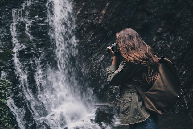 A beleza da natureza deve ser capturada. jovem mulher moderna com mochila fotografando água em pé perto da cachoeira
