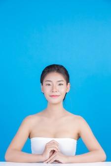 A beleza das mulheres com imagens perfeitas de saúde da pele tocando em seu rosto e sorrindo como um spa para cuidar de sua pele azul