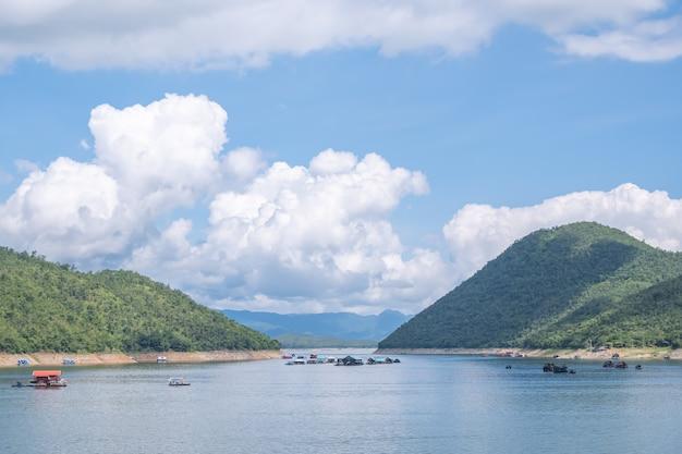 A beleza dentro da barragem e a casa flutuante no céu brilhante na barragem de sri nakarin, kanchana buri na tailândia.