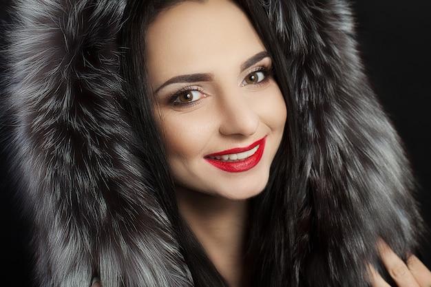 A beleza é uma menina modelo em um casaco de pele preto. mulher de luxo inverno linda.