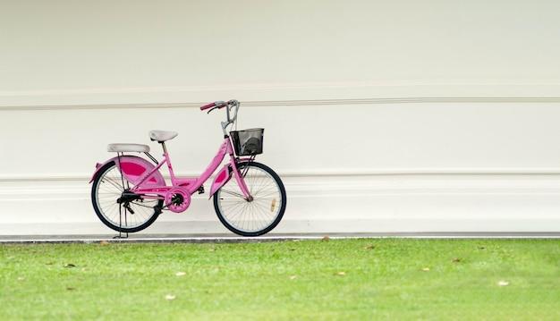 A bicicleta cor-de-rosa estacionou na frente das paredes coloridas creme. a frente da grama verde.