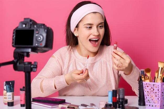 A blogueira de beleza com câmera grava novo vídeo para seu vlog. morena fêmea anuncia produtos cosméticos