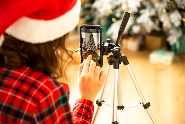 A blogueira de uma garota grava um vídeo ou uma foto em seu telefone no fundo de uma árvore de natal. ela colocou um chapéu de papai noel.