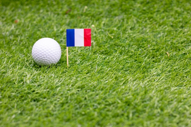 A bola de golfe com a bandeira de france está na grama verde.