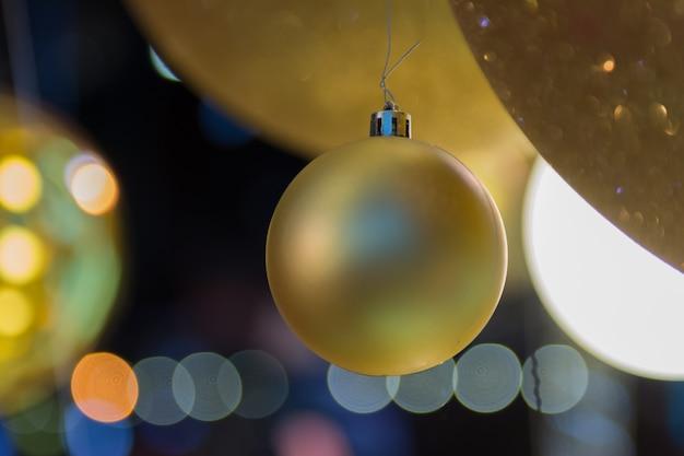 A bola e a noite douradas abstratas bokeh, cidade iluminam-se para o fundo.
