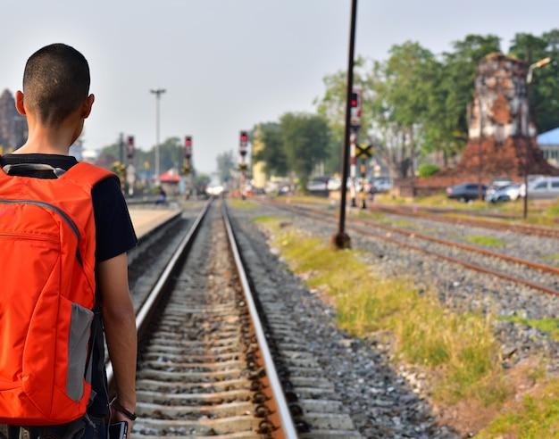 A bolsa vermelha de ombro de menino sozinha entra em rialway para esperar de estação para trem chegar.