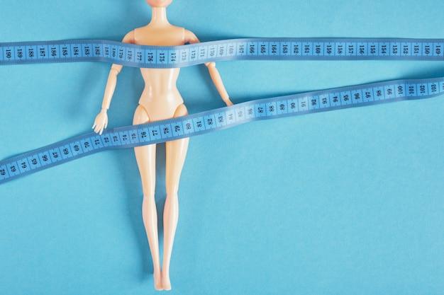 A boneca é enrolada com fita métrica, culto ao conceito de magreza e anorexia, dieta e emagrecimento