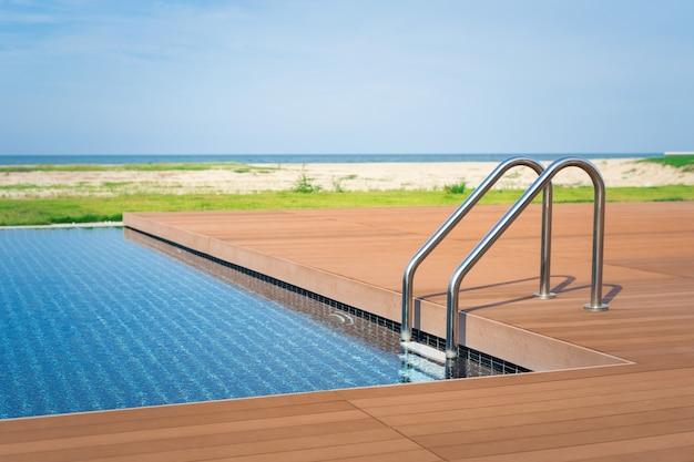 A borda piscina luxuosa com escada e deck de madeira em hotel na praia.