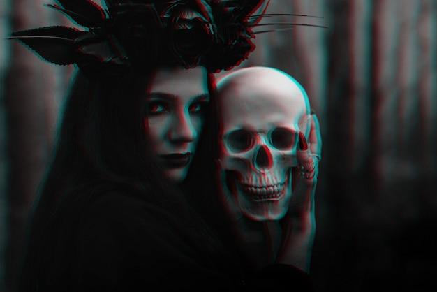 A bruxa malvada assustadora em trapos pretos segura o crânio de um homem morto nas mãos para um ritual sombrio. preto e branco com efeito de realidade virtual de falha 3d