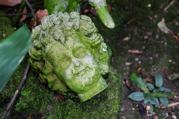 A cabeça da estátua de cimento no jardim
